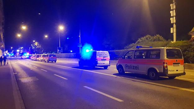 mehrere Polizeiautos in der Nacht auf einer Strasse parkiert