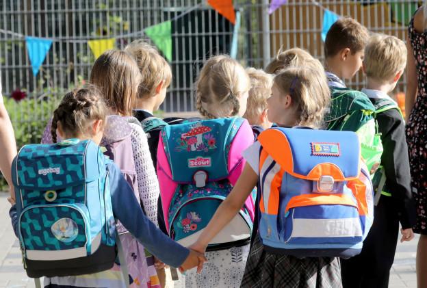Eine Gruppe junger Schülerinnen mit Thek steht vor einer Schule