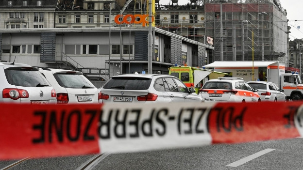 Ein Polizeiband-Sperrzone, dahinter Autos