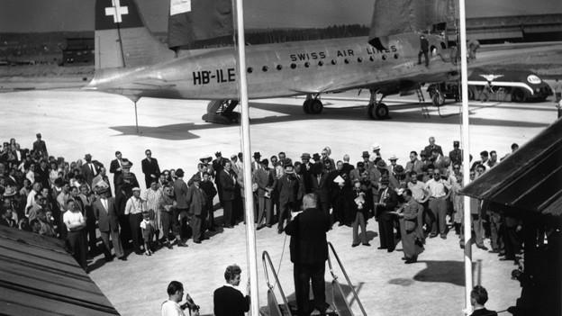 schwarz-weiss Bild, im Vordergrund ein Mann, der auf einer Flugtreppe steht und eine Rede hält, im Hintergrund Zuhörer und ein Swissair-Flugzeug