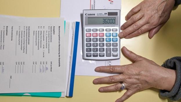 Hände, Rechner und Rechnungen