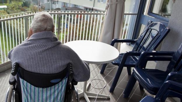 Eine Altersheimbewohnerin im Rollstuhl auf einem Balkon.