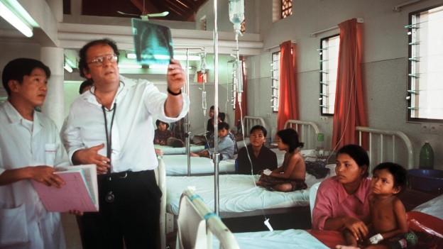 Ein Arzt vor Spitalbetten schaut sich ein Röntgenbild an.