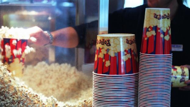 Ein Kinomitarbeiter füllt Popcorn in einen grossen Becher.