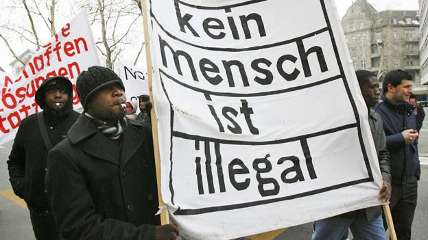 Dunkelhäutige Menschen halten ein Trasparent mit der Aufschrift: kein Mensch ist illegal