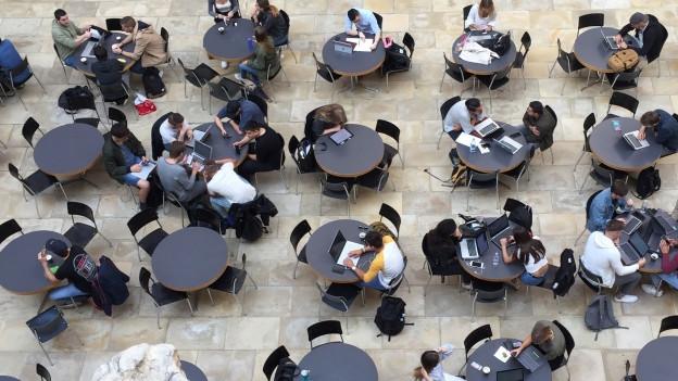 Blick in den Lichthof des Uni-Hauptgebäudes - an den Tischen sitzen Studenten
