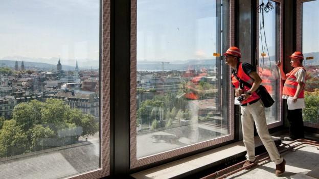 2 Männer blicken aus einem Rohbau auf die Stadt Zürich hinunter.
