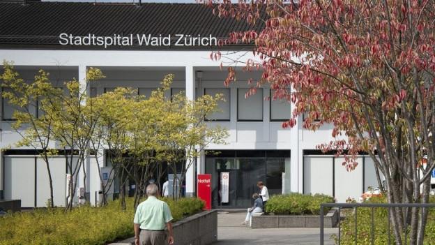 Ein Mann läuft vorbei an einem Baum in Richtung Eingang des Waidspitals.