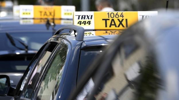 Taxis stehen hintereinander in einer Schlange.