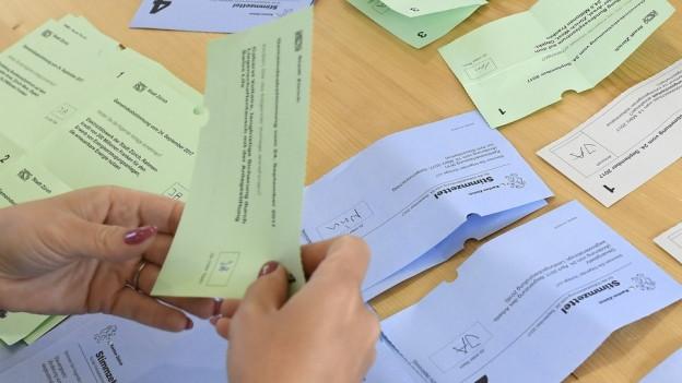 Wahllehlfer sortieren Abstimmungszettel