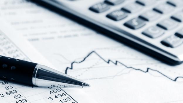 Ein Kugelschreiber und ein Rechner liegen auf Rechnungsunterlagen.