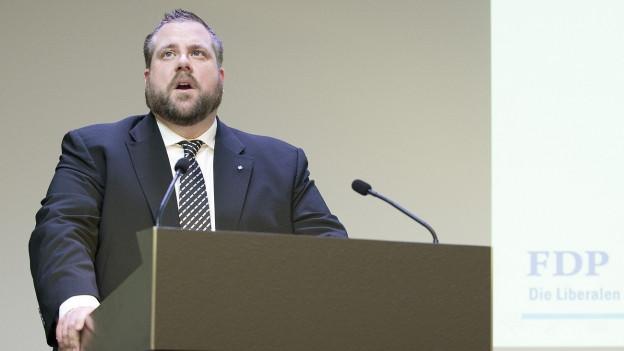 Ein Mann mit Bart spricht an einem Rednerpult