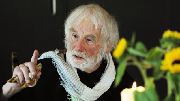 Ein Mann mit Bart und weissem Haar spricht mit erhobenem Zeigefinger.