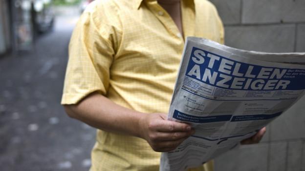 Ein Mann hält einen Stellenanzeiger in den Händen und liest.