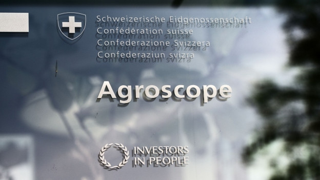 Das Wort «Agroscope» auf einer Glastür, dahinter blauer Himmel