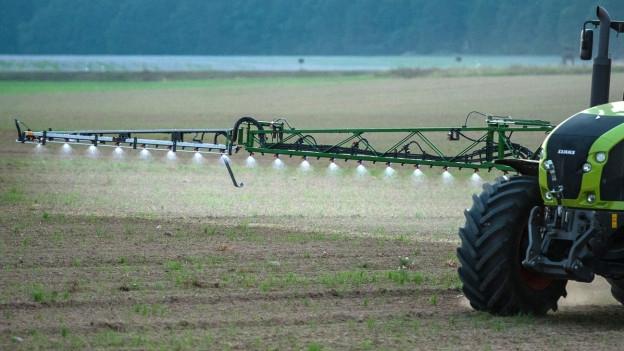 Ein Traktor bringt Spritzmittel auf ein Feld aus