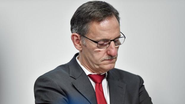 Ein Mann mit Krawatte blickt traurig nach unten.