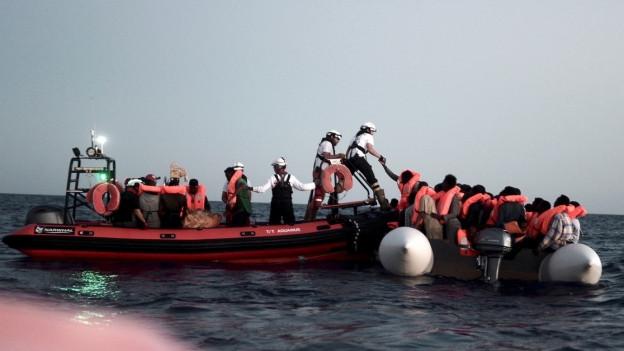 Flüchtlinge wechseln auf dem Mittelmeer von einem Schlauchboot in ein etwas grösseres.