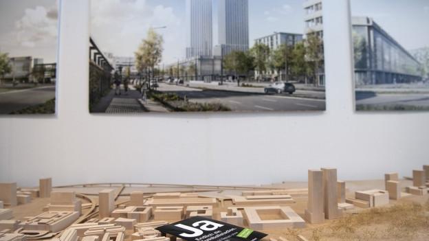 Ein Flyer mit der Ja-Parole liegt auf einem Holzmodell des neuen Fussballstadions, im Hintergrund ein Bild des Stadions.