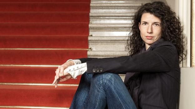 Eine Frau in Jeans und Jacke sitzt auf einer Treppe
