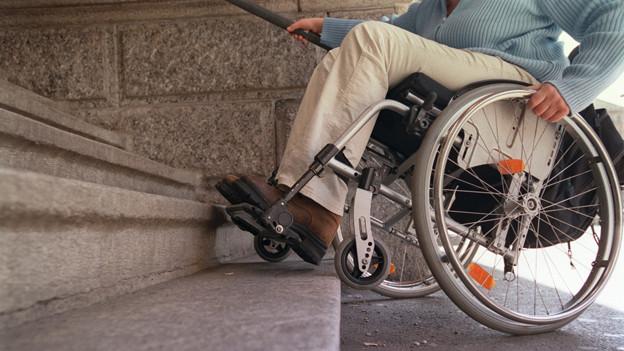 Ein Rollstuhlt steht an einer Treppe an.