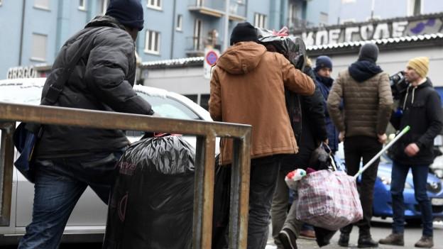 Menschen mit Mützen tragen Abfallsäcke und andere Taschen