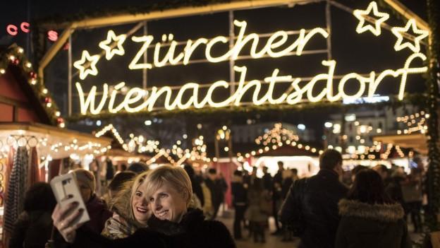 Der Eingangsbereich des Weihnachtsdorfs auf dem Sechseläutenplatz in Zürich ist hell beleuchtet.