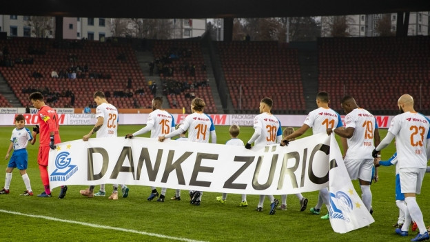 """Fussballspieler tragen ein Banner mit der Aufschrift """"Danke Zürich"""" vom Fussballfeld"""