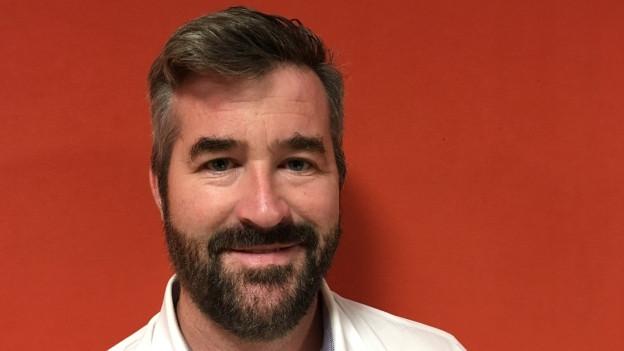 Ein Mann mit Bart steht vor einer orangen Wand.