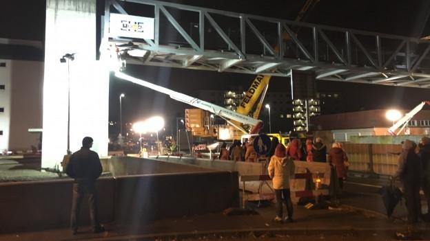 Leute aus dem Quartier schauen nachts dem Bau einer Fussgängerbrücke zu.