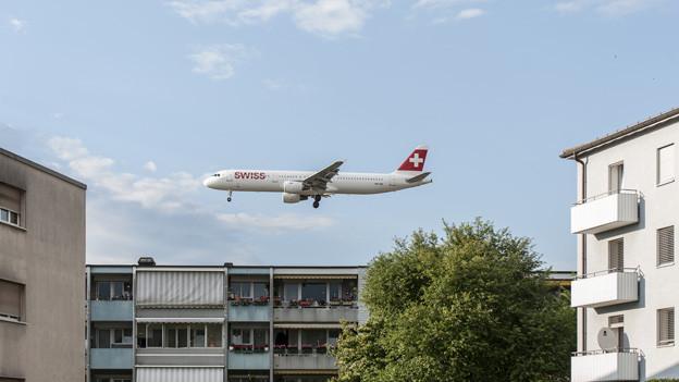 Ein Flugzeug fliegt sehr tief über eine Wohnsiedlung.