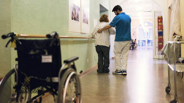 Ein Pfleger stützt einen Senioren im Gang eines Alterszentrums.
