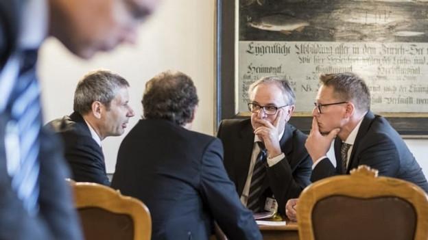 Eine Gruppe von Männern sitzt am Tisch und ist in ein Gespräch vertieft.
