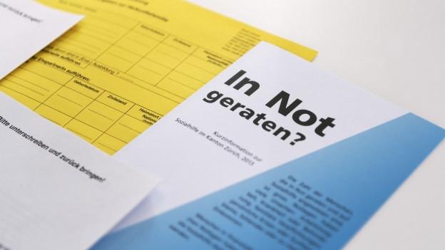 Eine Broschüre der Sozialhilfe liegt auf dem Tisch.