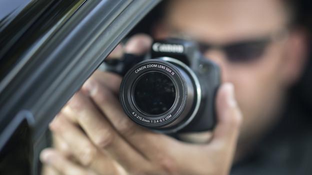 Ein Mann blickt durch eine Kamera aus einem Autofenster