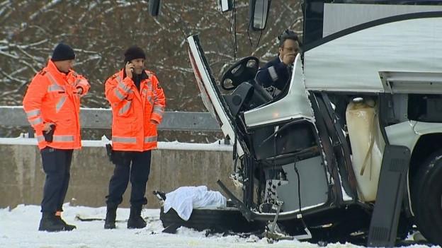 Zwei Polizisten stehen am Autobahende neben dem Wrack des Unglücksbusses.