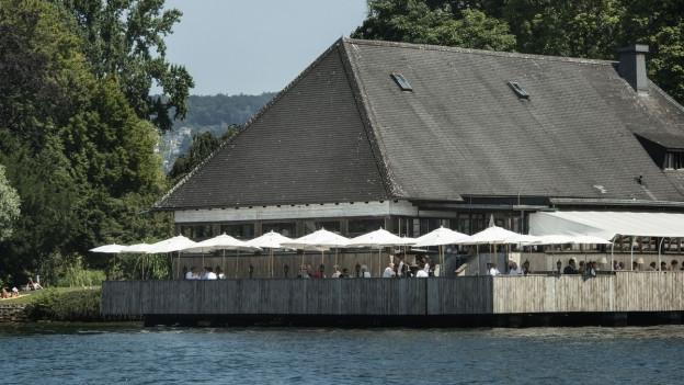 Das Restaurant «Fischerstube» liegt direkt am Zürichsee, weisse Schirme stehen auf der Terrasse.