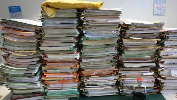 In einem Büro stapelnsich Akten auf einem Schreibtisch.