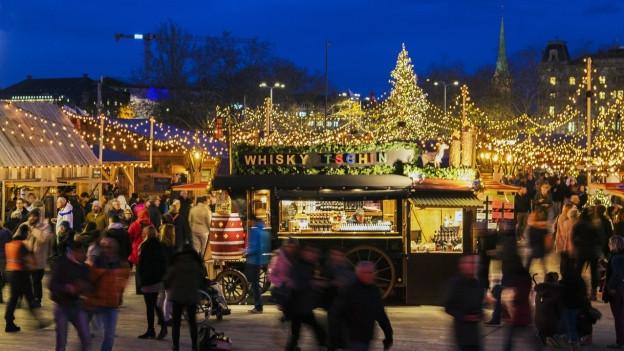 Blick auf einen Weihnachtsmarkt mit Glühweinstand.