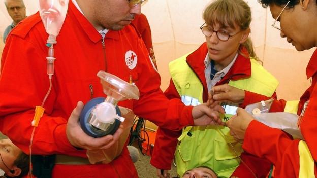 Zwei Samariter stehen neben einem Mann und halten eine Beatmungsflasche.