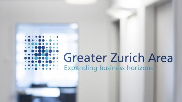 """Eine Glasscheibe in einem Büro mit der Aufschrift """"Greater Zurich Area""""."""