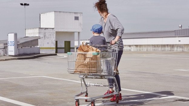 Frau mit Einkaufswagen und Kind auf leerem Platz