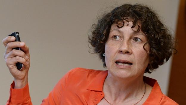 Frau mit dunklen Locken und oranger Bluse