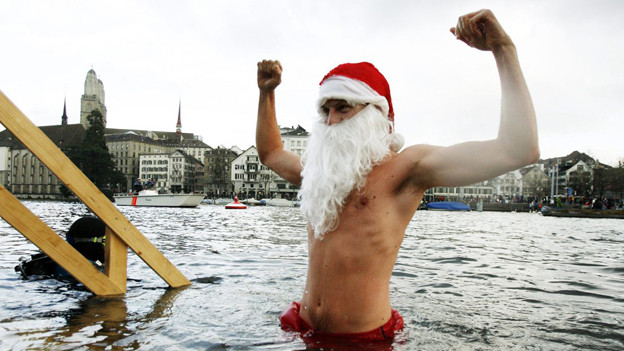 Ein Mann steigt in Siegerpose aus der winterlichen Limmat