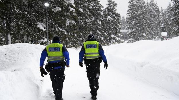 Zwei Polizisten gehen durch einen verschneiten Wald.