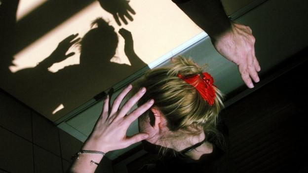 Gestellte Szene, wie eine Frau den Schlägen eines Mannes im Schlafzimmer ausweicht.