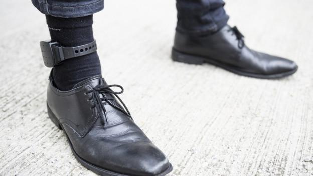 schwarzer Herrenschuh, schwarze Socken, darum ein schwarzes Kästchen befestigt.