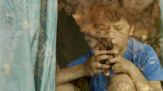 Ein Kind sitzt hinter einem Vorhang und tippt in sein Handy