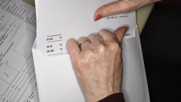 Eine Hand nimmt eine Rechnung aus dem Briefumschlag.