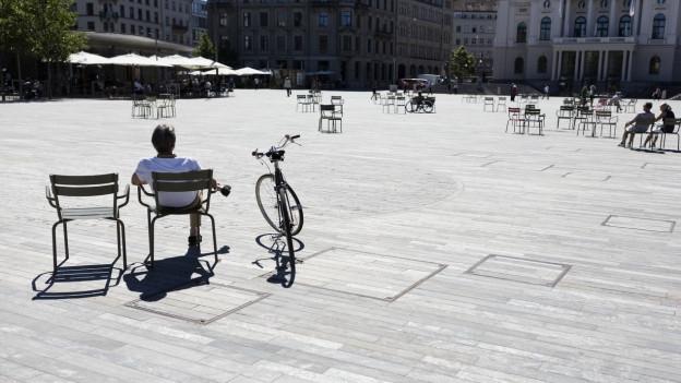 Menschen geniessen die Sonne auf dem freien Sechseläutenplatz